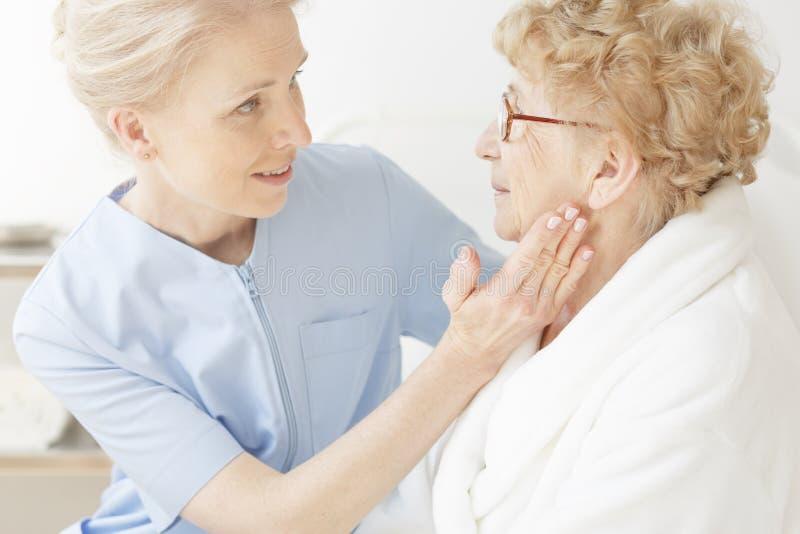 Friendly nurse comforting elderly woman royalty free stock photography
