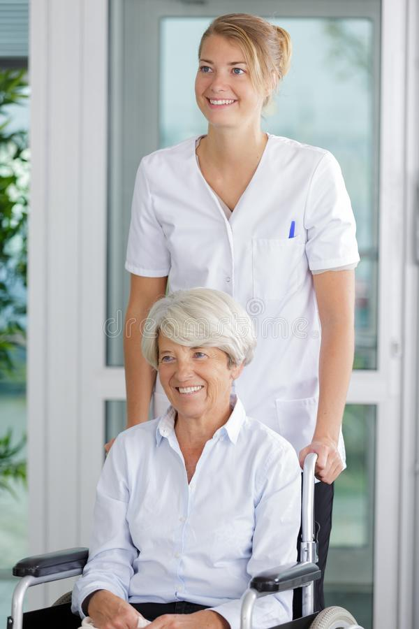Friendly nurse with senior woman in wheelchair. Friendly nurse with senior women in the wheelchair royalty free stock photos