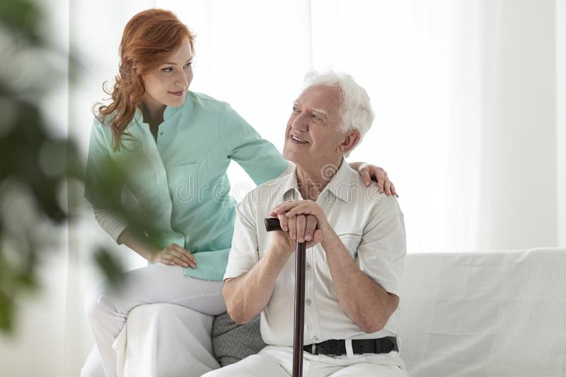 Friendly nurse and smiling elderly man with walking stick in the stock image