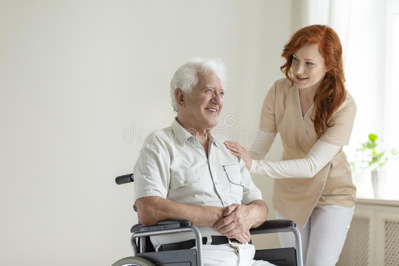 Friendly nurse supporting smiling paralyzed senior man in a whee stock photos