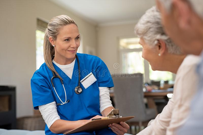 Friendly nurse talking with old couple. Happy nurse talking to senior patients in private clinic. Senior couple consulting health and medical report with doctor royalty free stock photo
