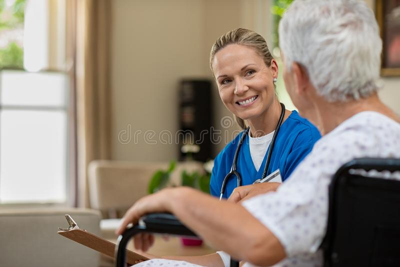 Friendly nurse talking to senior patient royalty free stock photo