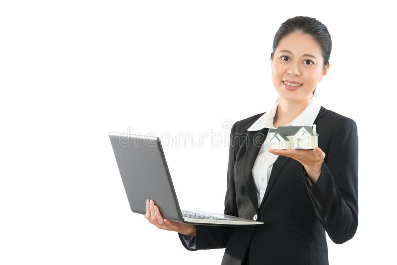 Friendly office worker lady showing model. Friendly office worker lady holding showing miniature house model and mobile laptop computer working online with stock photo