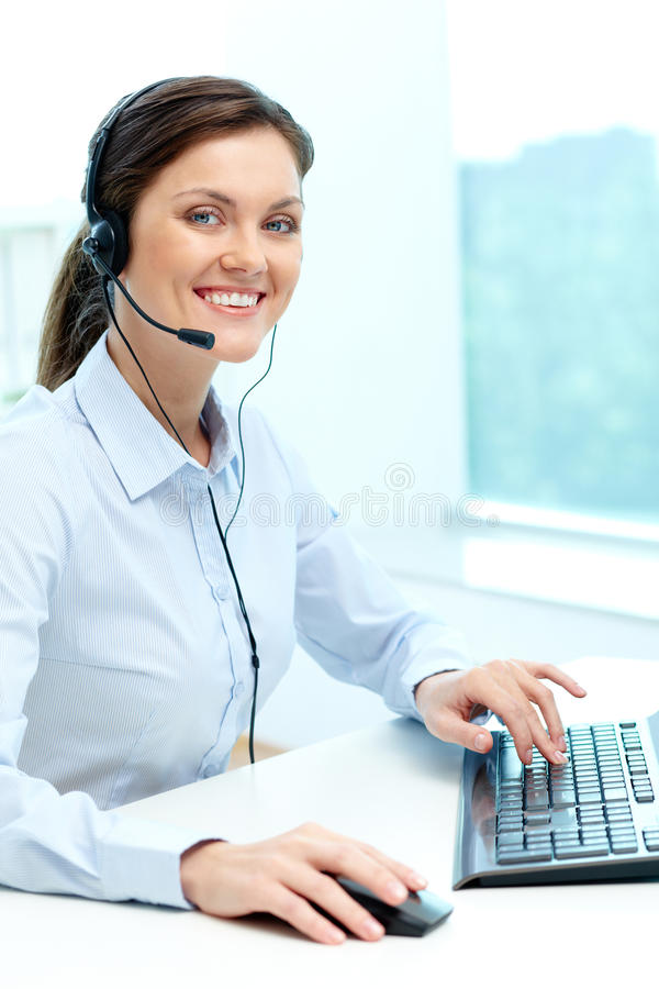 Friendly operator. Portrait of young operator with headset looking at camera with friendly smile stock photo