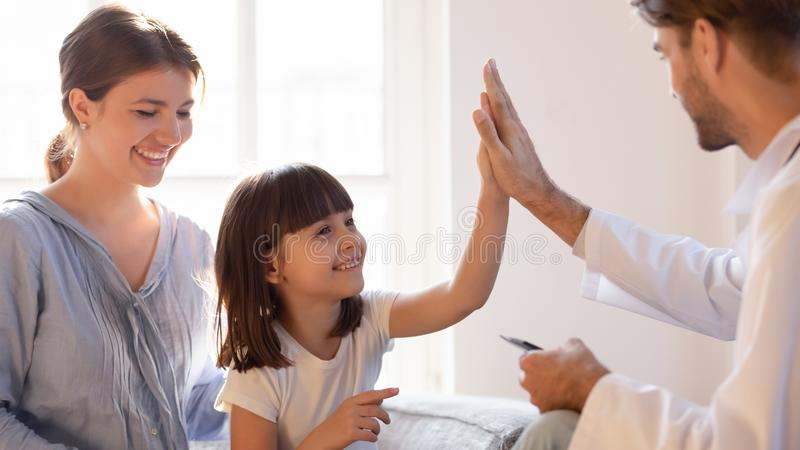 Friendly pediatrician doctor giving high five to little girl patient royalty free stock photography