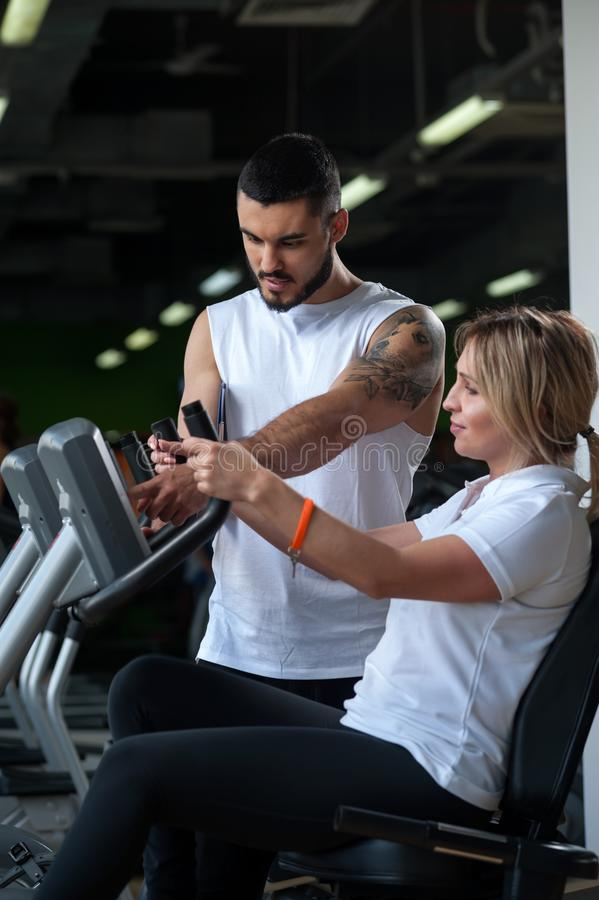 Friendly personal coach with female client in gym. stock image