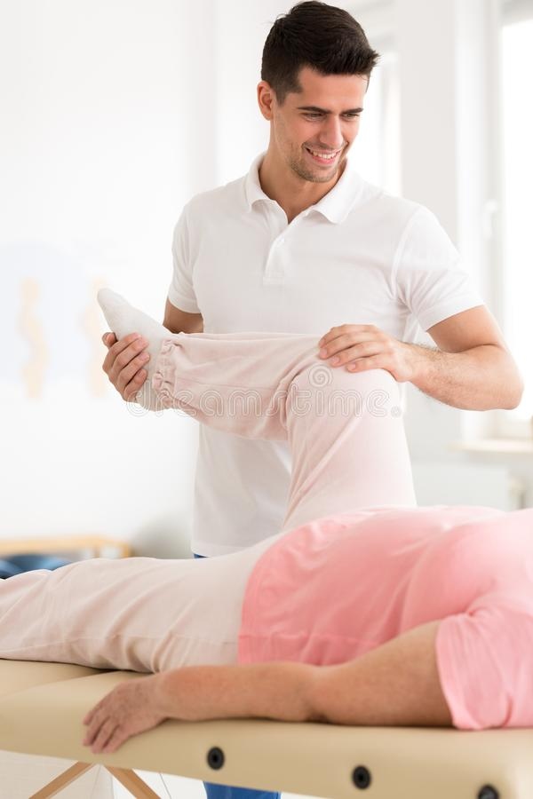 Physiotherapist bending patient`s leg stock images