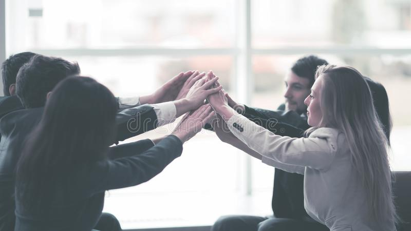 Friendly professional business team, pleased with his victory, hands clasped together royalty free stock image