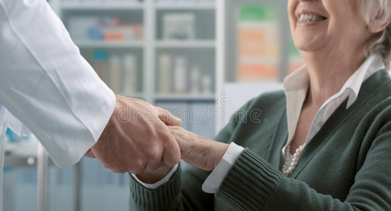 Friendly professional doctor holding a senior patient`s hands stock images