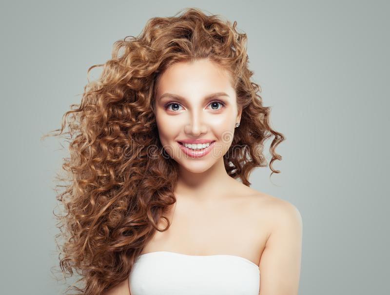 Friendly redhead girl portrait. Cheerful woman with long healthy curly hair stock photography