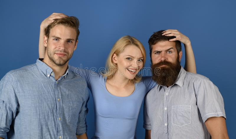Friendly relations. Girl and guys happy together. Woman hugs two men. More than friends. True friendship and human. Relations. Group friends hug blue background stock photography