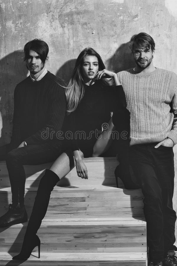 Friendly relations. Pretty girl sitting with two bearded men. Friendly relations. Pretty girl with long blond hair in black bodysuit and knee high boots sitting stock photography