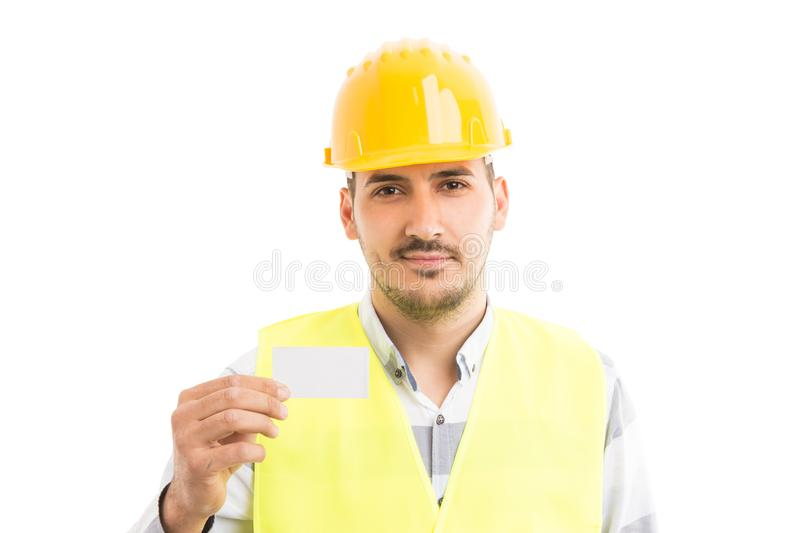 Friendly repairman holding and showing white empty business card royalty free stock photo