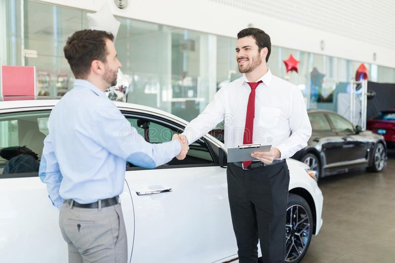 Friendly Seller Shaking Hands With Customer stock photography