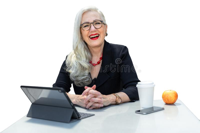 Friendly senior advisor, consultant, manager, business person CEO, sitting at desk with a friendly smile, isolated on white backgr stock photography