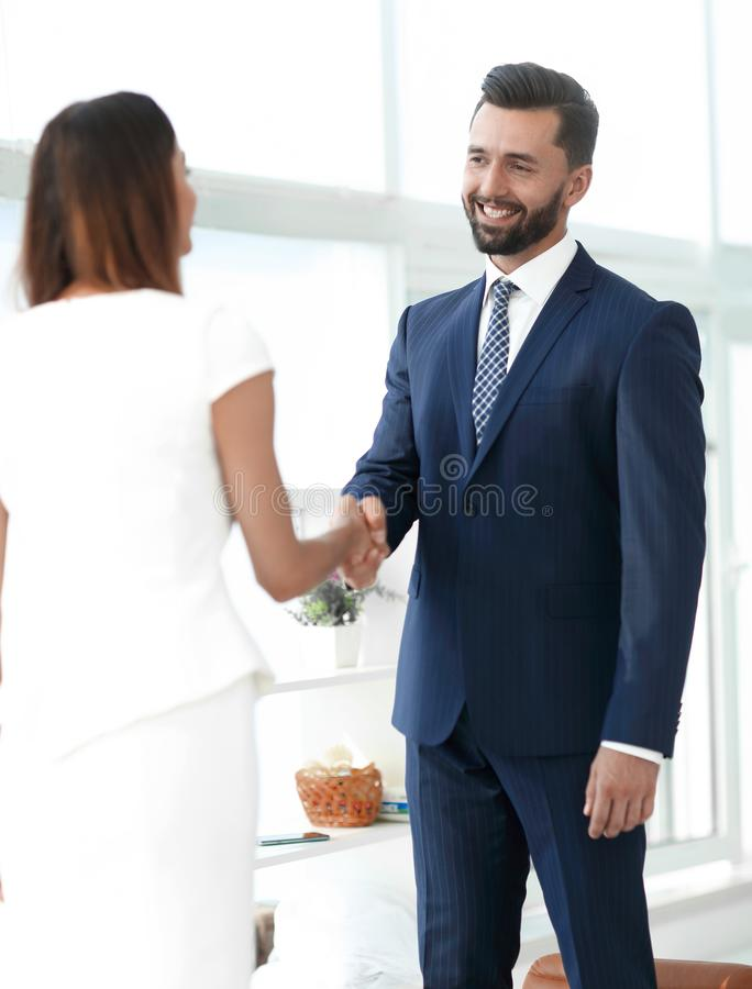 An attractive business man and woman team shaking hands. Friendly senior businessman handshaking with young businesswoman in office stock photos