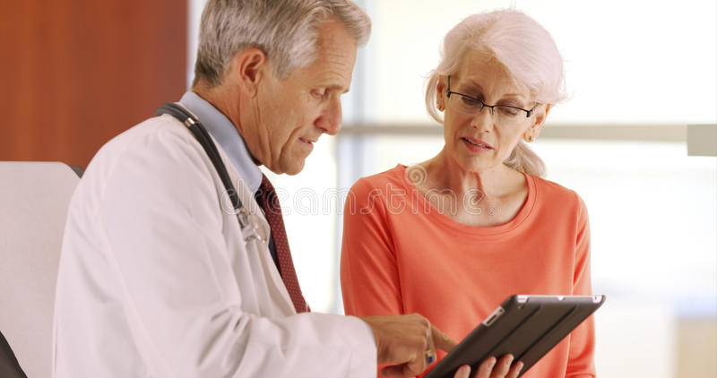 Friendly senior doctor talking with elderly woman patient in the office royalty free stock photography
