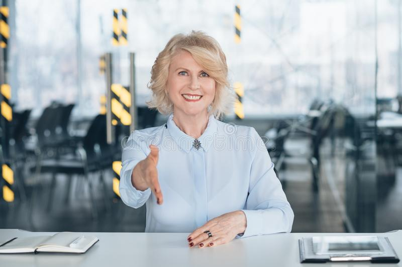 Friendly senior lady welcoming successful company stock photos