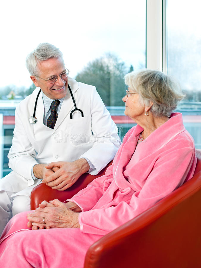 Friendly senior male doctor chatting to a patient. stock images