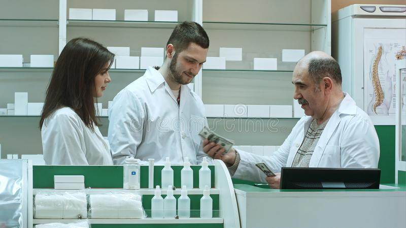 Friendly senior pharmacist give salalry dollar to his yunger colleagues stock photography