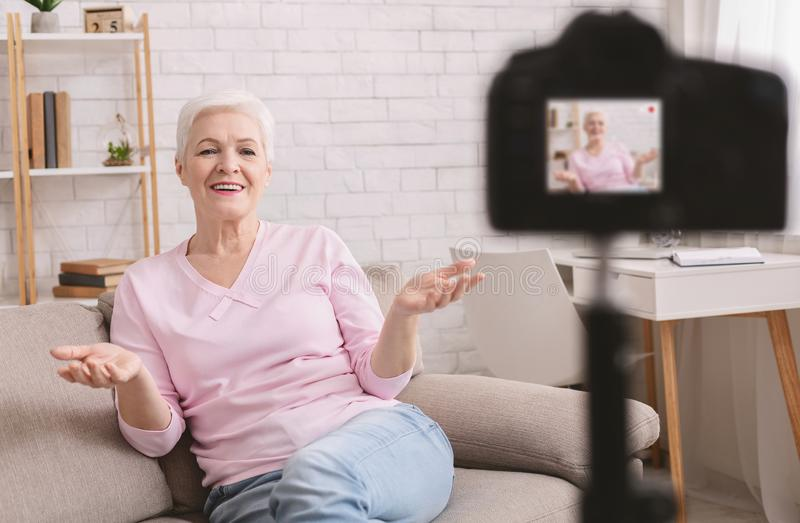 Friendly senior woman vlogger sitting on sofa dating online royalty free stock images