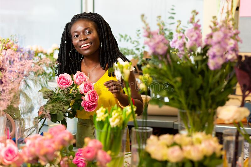 Amazing international female person being in all ears. Friendly smile. Kind florist expressing positivity while holding bouquet of roses stock photography