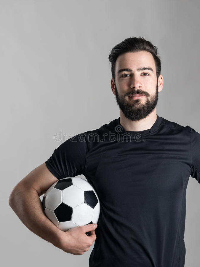 Friendly smiling bearded soccer player holding ball under his arm looking at camera. Over gray studio background royalty free stock photography