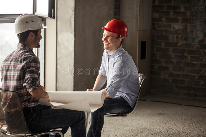 Friendly smiling builders` team resting on the chairs royalty free stock photos