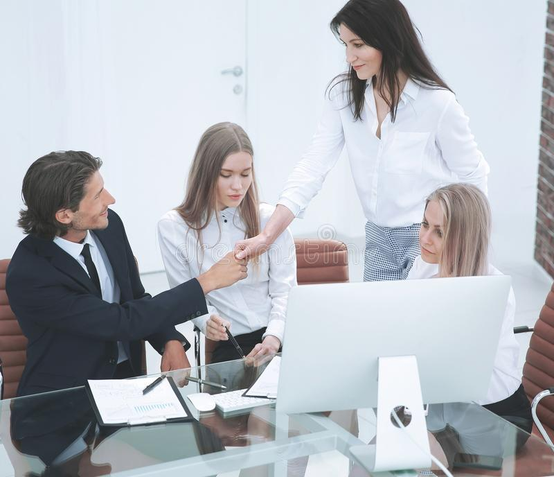 Friendly smiling businessman and businesswoman handshaking over the office desk stock images