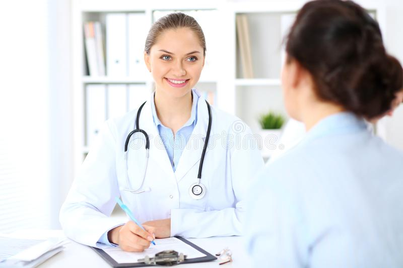 Friendly smiling doctor and patient sitting at the table royalty free stock photo