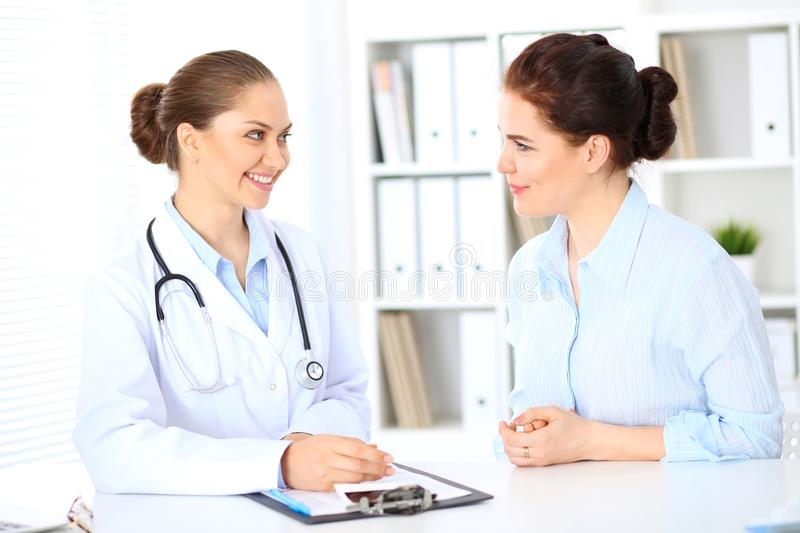 Friendly smiling doctor and patient sitting at the table stock photos