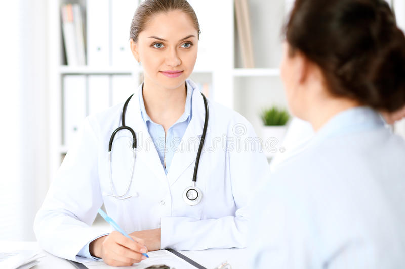 Friendly smiling doctor and patient sitting at the table stock images