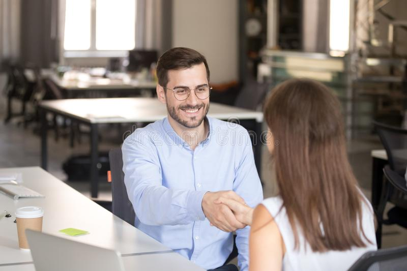 Friendly smiling employee shaking hand with young woman. Newly hired office worker meeting with female colleague, first day at work, applicant, intern, trainee royalty free stock photography