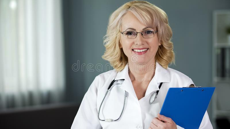 Friendly and smiling lady doctor looking into camera, giving hope for recovery. Stock photo royalty free stock images