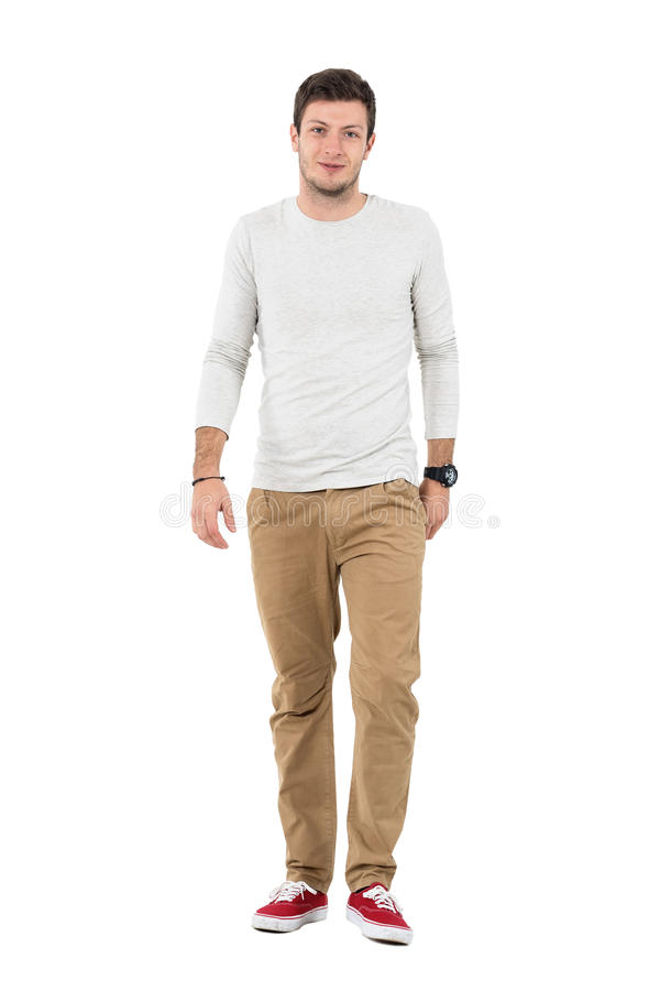 Friendly smiling man in beige pants walking towards camera. Full body length portrait isolated over white studio background stock image