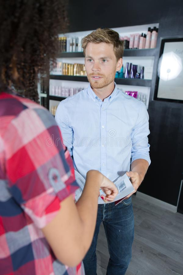 Friendly smiling man hairdresser discussing with woman client royalty free stock photos