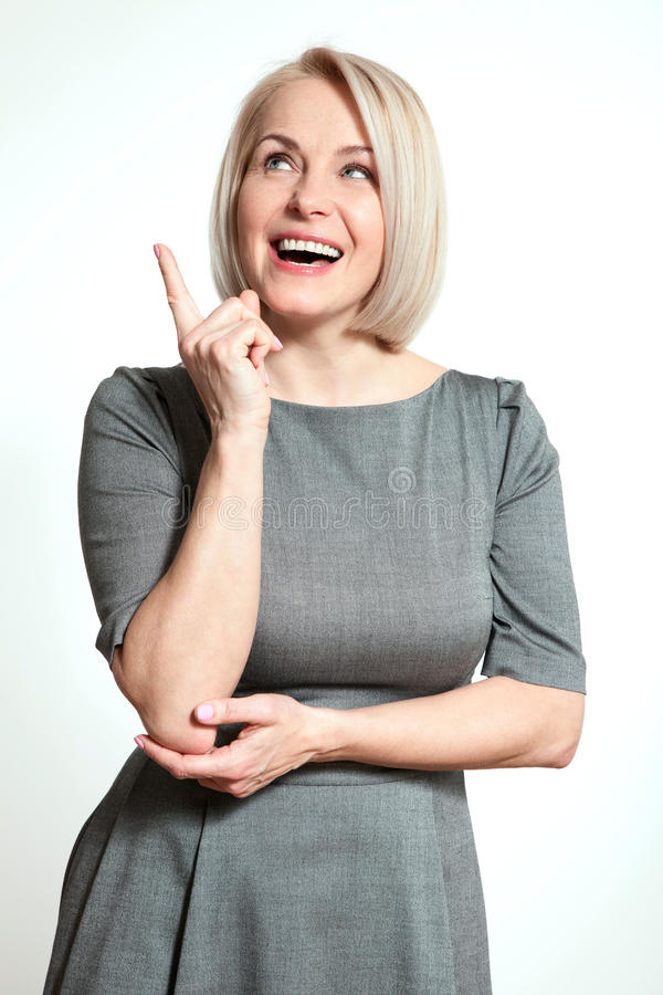 Friendly smiling middle-aged business woman pointing at copyspace on white background stock images
