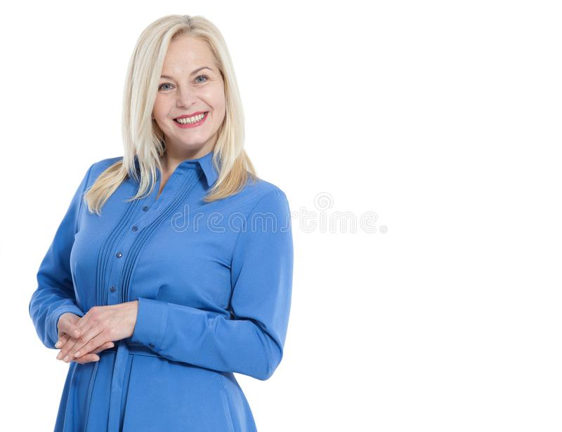 Friendly smiling middle aged woman in blue dress isolated stock photography