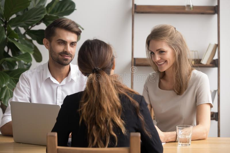 Friendly smiling partners meeting female client or job candidate. Sitting at table in office. HR managers advisors listening answer young trainee, convincing stock photos