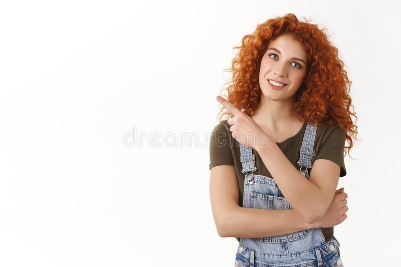 Friendly stylish caucasian redhead curly-haired woman invite coworkers bar after work, pointing finger left blank copy stock photography