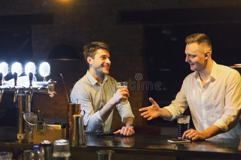 Two happy young men talking and drinking beer at bar stock photo