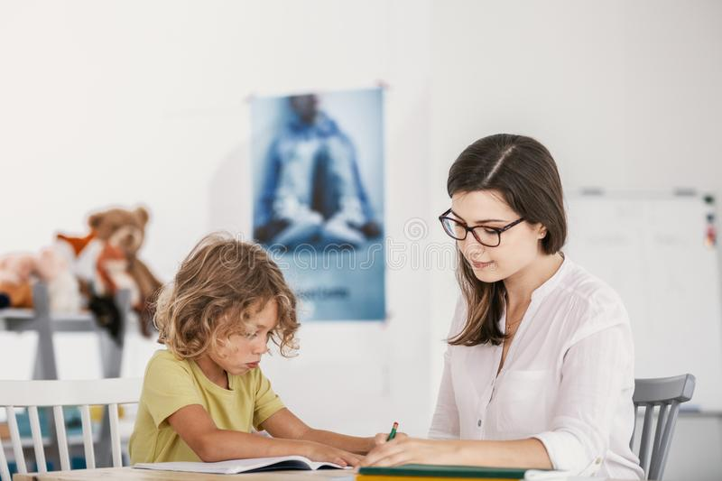 Friendly teacher doing homework with young boy stock photography