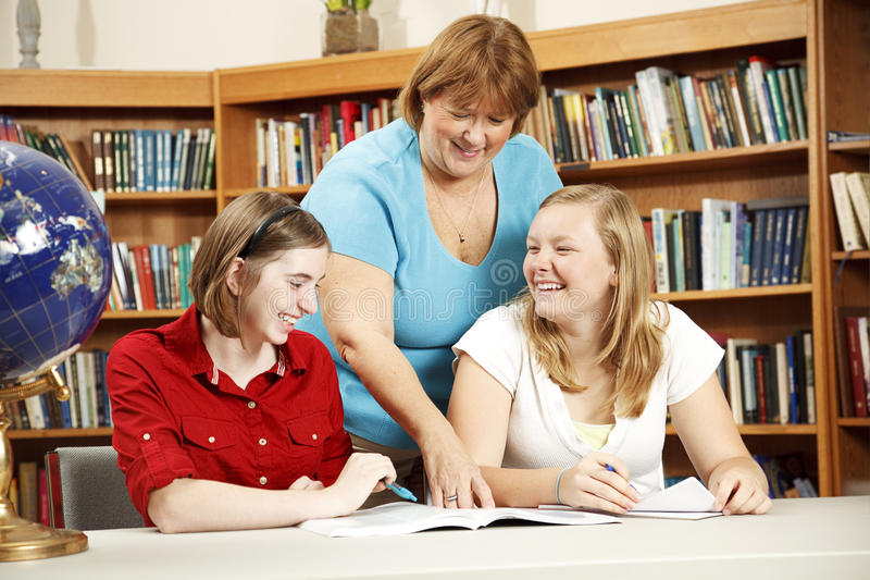 Friendly Teacher Helping Students Stock Photo