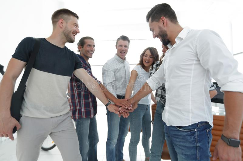 .friendly team of designers clasped their hands together royalty free stock images