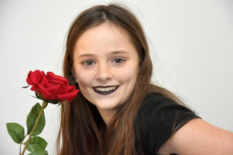 Friendly teenage girl with black painted lips and red rose stock photo