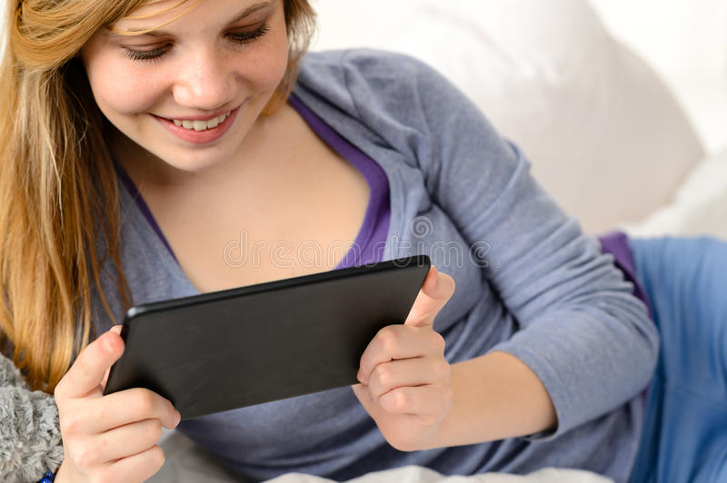 Friendly teenage girl reading on digital tablet royalty free stock photography
