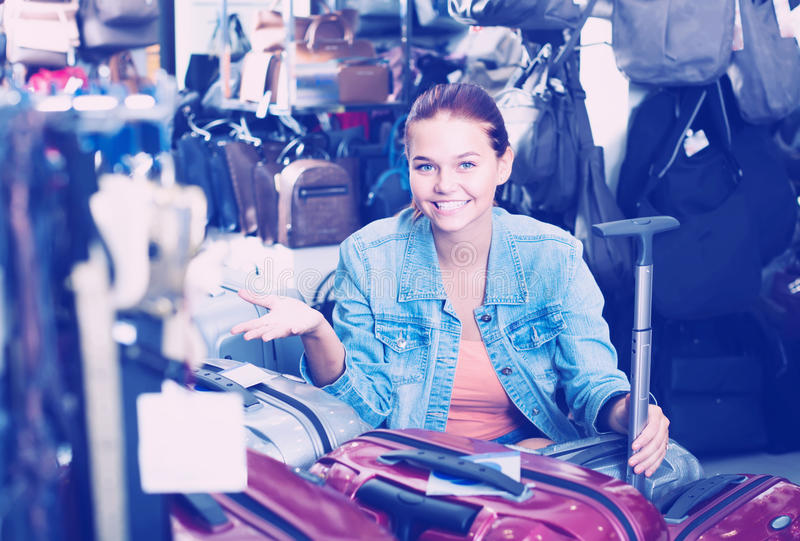 Friendly teenager girl choosing new large plastic luggage bag stock images