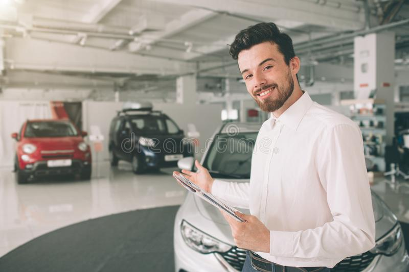 Friendly vehicle salesman presenting new cars at showroom. Photo of young male consultant showing new car in auto show royalty free stock photos