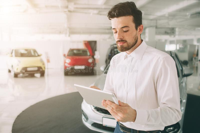 Friendly vehicle salesman presenting new cars at showroom. Photo of young male consultant showing new car in auto show stock images