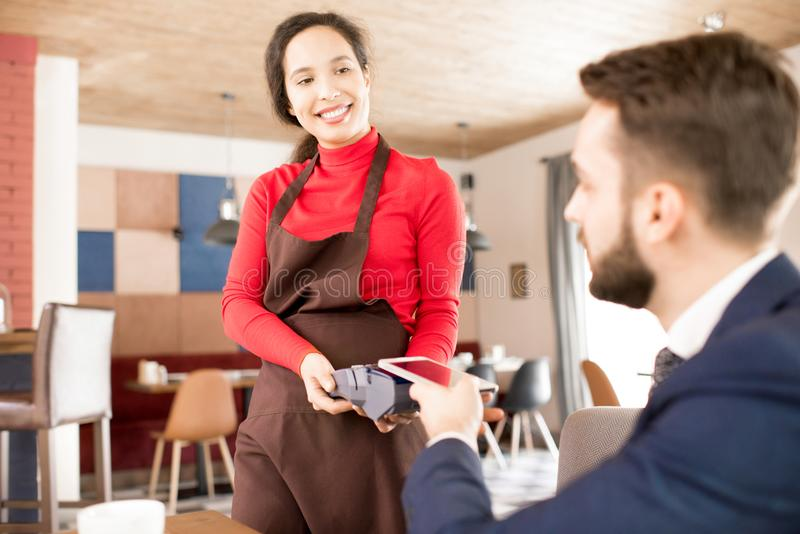 Friendly waitress taking payment from guest. Cheerful friendly attractive young mixed race waitress in apron smiling at restaurant guest who paying for lunch stock photos